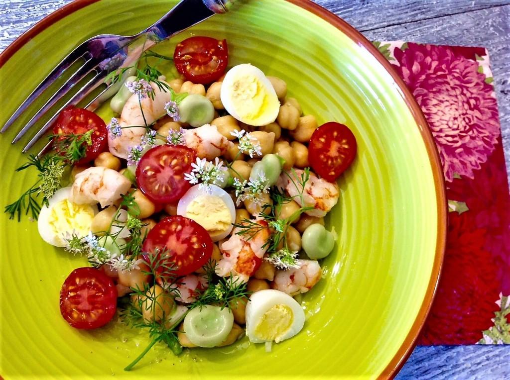 ensalada de garbanzos, habas, cherrys, huevos de codorniz, flor de cilantro, cebolla, pimiento verde