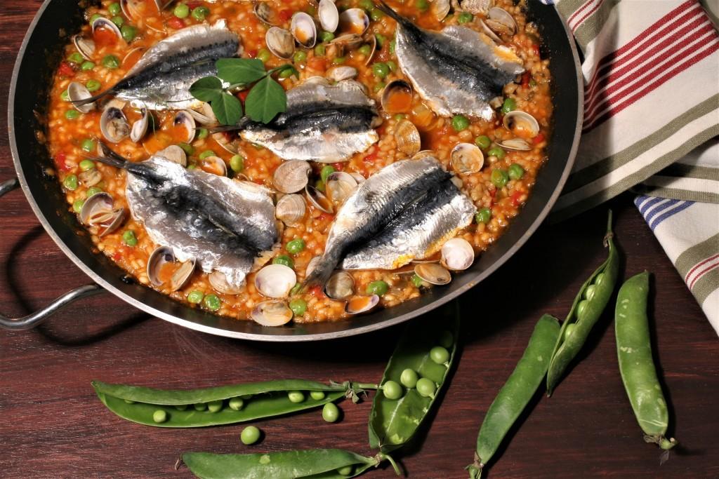 arroz de sardinas, chirlas y guisantes.